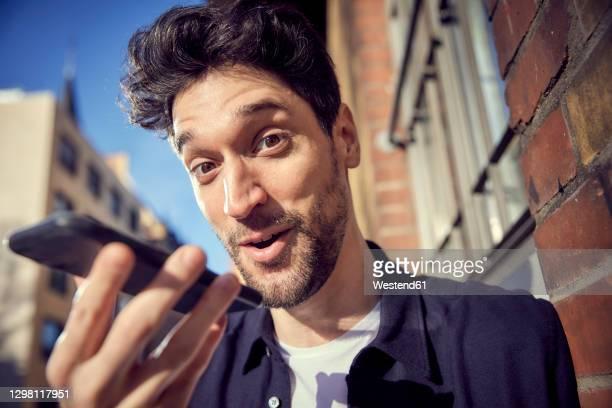 happy businessman talking on mobile phone while standing outdoors - homens de idade mediana imagens e fotografias de stock