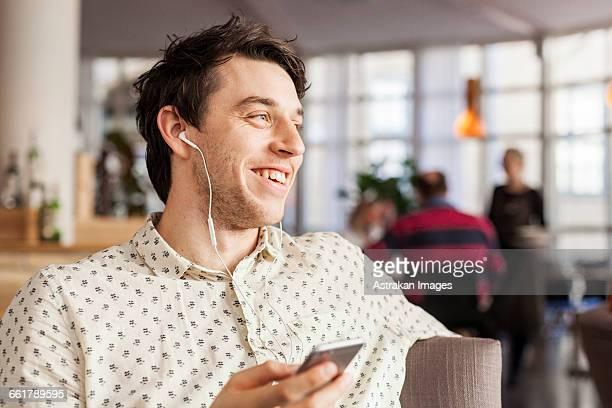Happy businessman talking through earphones at restaurant