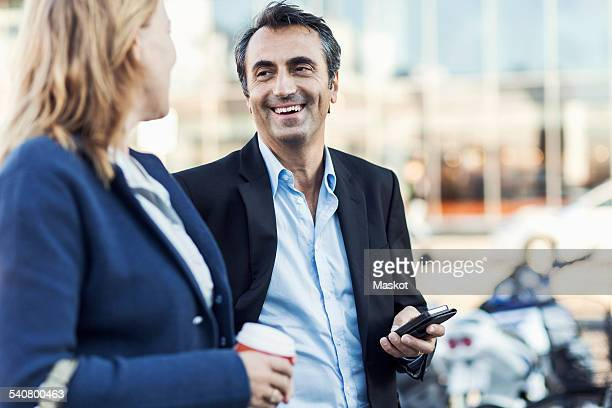 Happy businessman talking to female colleague outdoors