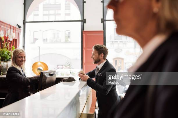 Happy businessman talking to female receptionist at hotel reception