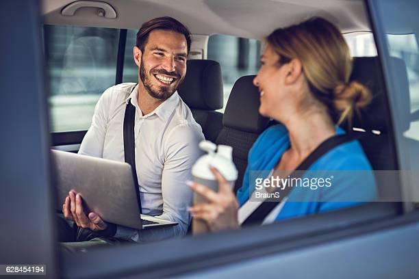 Heureux homme d'affaires femme parlant à son collègue dans la voiture.
