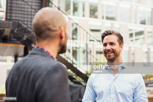 Happy businessman talking to male colleague at office yard