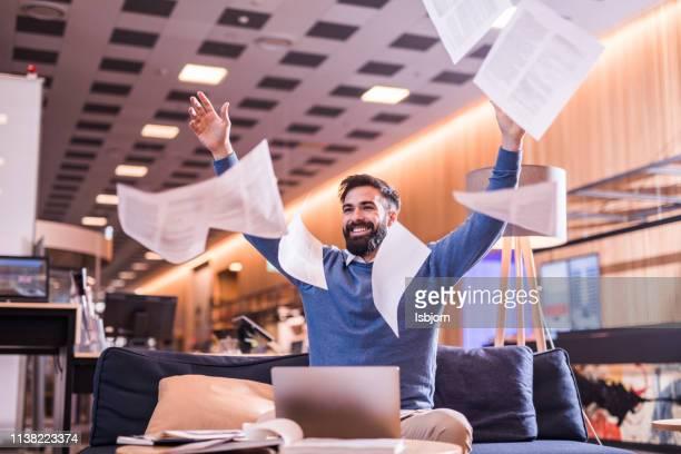 feliz hombre de negocios lanzando papeles. - bota fotografías e imágenes de stock