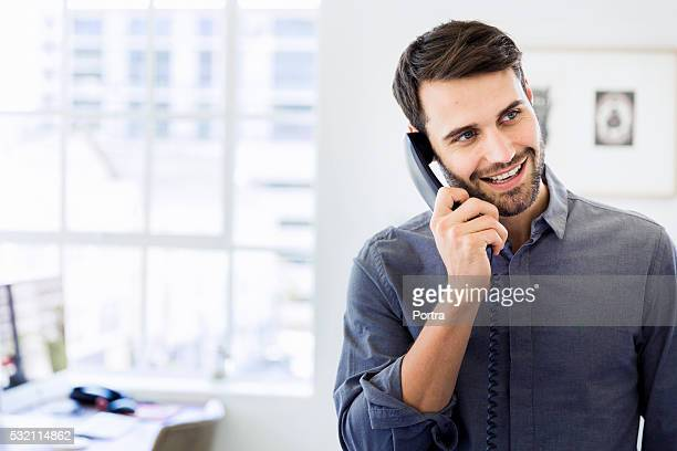 Happy businessman using landline phone in office