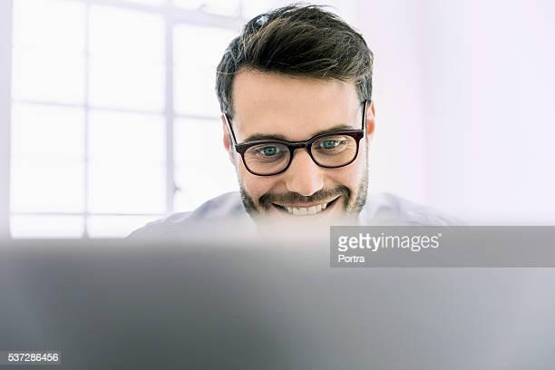 Glücklich Geschäftsmann benutzt Laptop im Büro