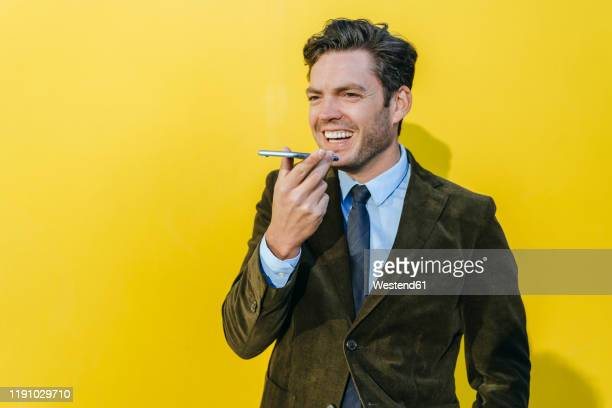 happy businessman using smartphone in front of yellow wall - brown coat stock pictures, royalty-free photos & images