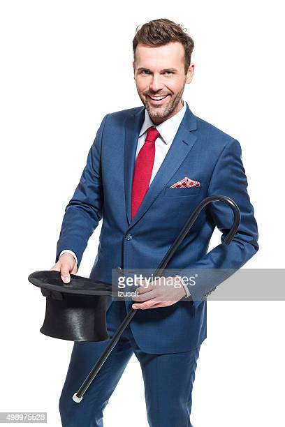 Happy businessman wearing suit, holding cylinder hat and walking cane