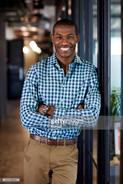 Happy businessman with arms crossed in office
