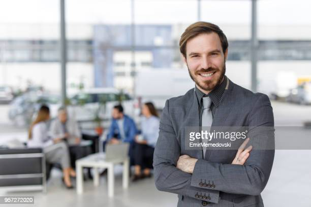 Happy businessman with business people in background