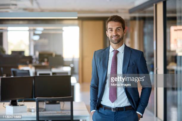 happy businessman with hands in pockets at office - 40 49 years stock pictures, royalty-free photos & images