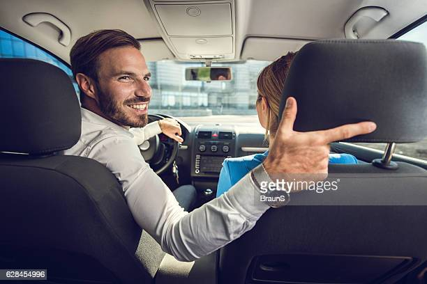 Happy businessman with his colleague driving reversing.