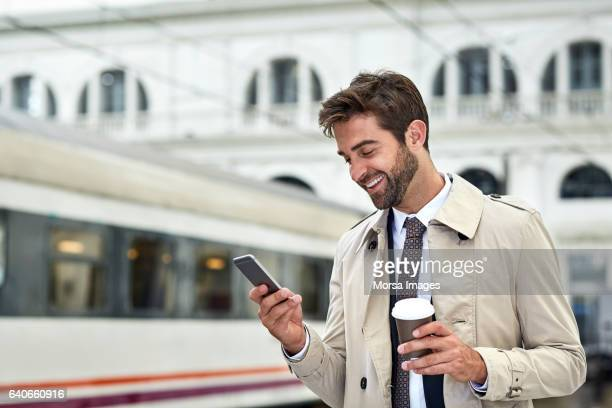 Happy businessman with phone and coffee at station
