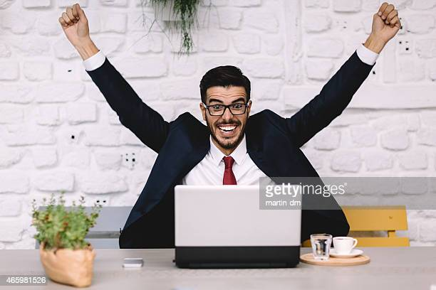 Happy businessman with raised hands