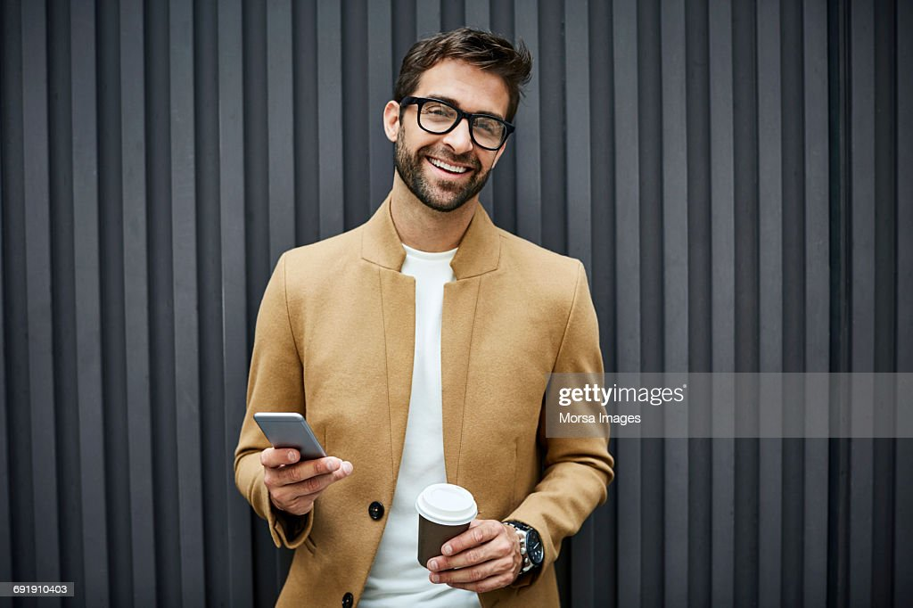 Happy businessman with smart phone and cup in city : Stockfoto