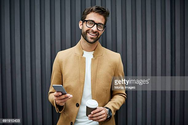 Happy businessman with smart phone and cup in city