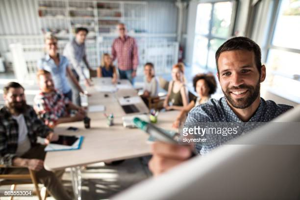happy businessman writing on whiteboard during business presentation in the office. - new business stock pictures, royalty-free photos & images