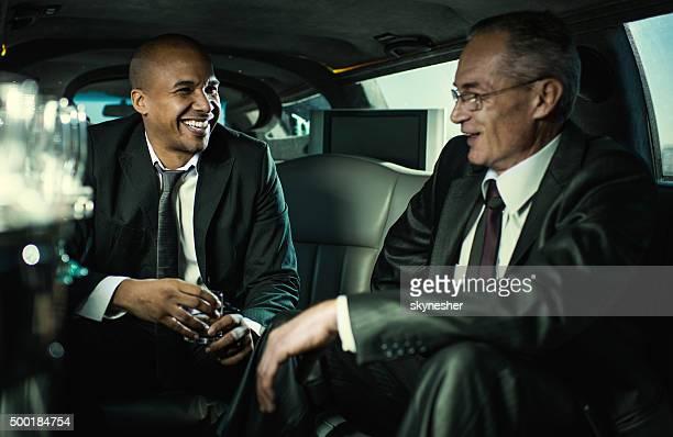 Glücklich Geschäftsleute Fahrt in einer limousine und sprechen.