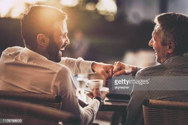 happy businessmen giving each other fist bump in street cafe at sunset. - fist bump stock pictures, royalty-free photos & images