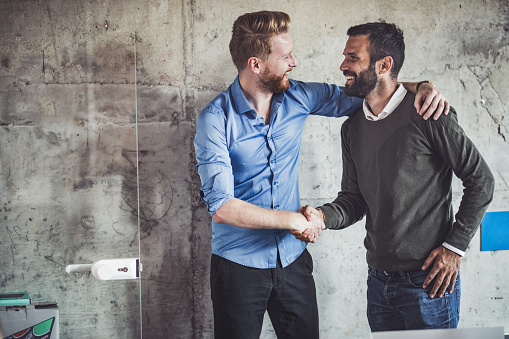 Happy businessmen greeting each other in the office. 1063731314