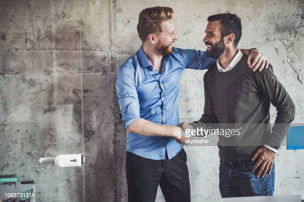 happy businessmen greeting each other in the office. - man made structure stock pictures, royalty-free photos & images