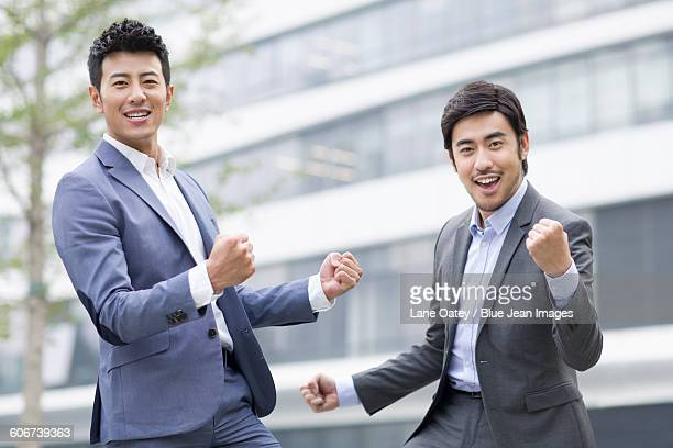 Happy businessmen punching the air