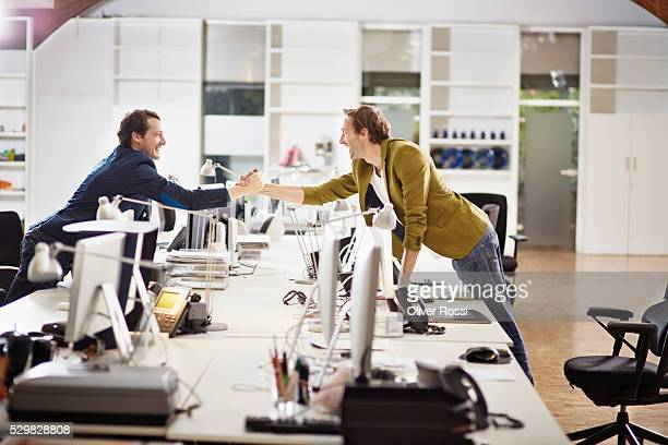 Happy businessmen shaking hands in office