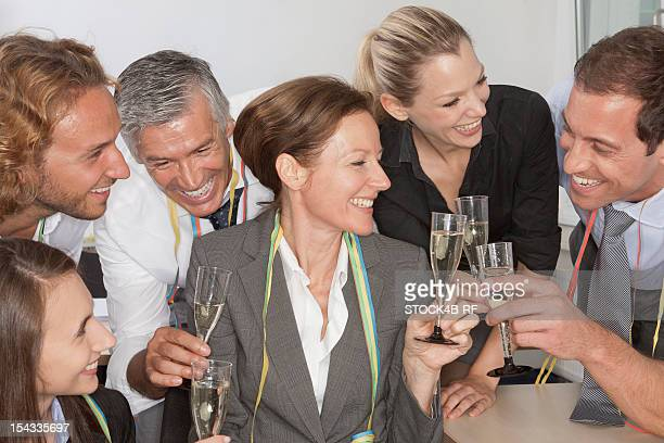 Happy businesspeople drinking champagne together
