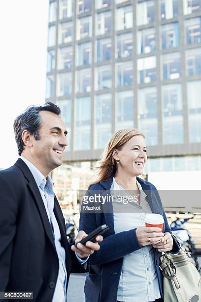 Happy businesspeople looking away while standing outside office building