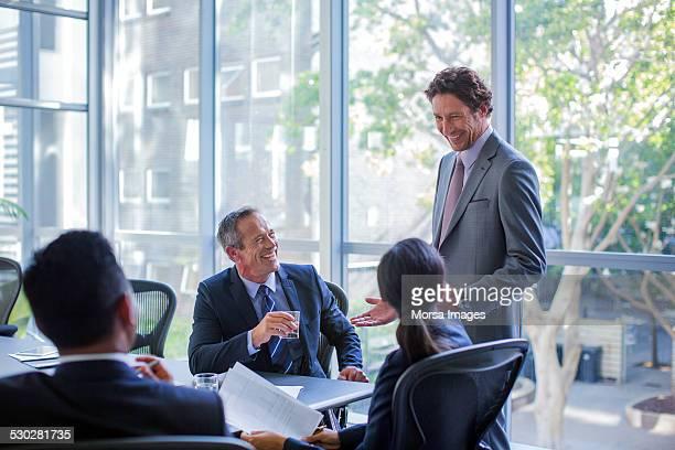 Happy businesspeople talking in board room