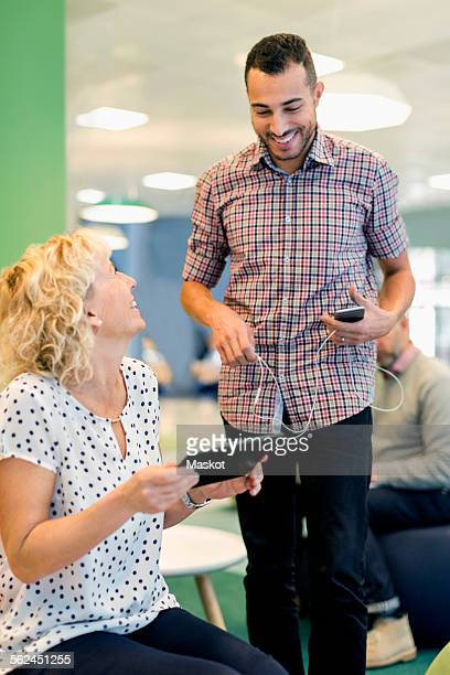 Happy businesspeople with technologies conversing at office lobby