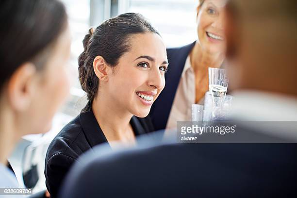 Happy businesswoman celebrating with colleagues in office