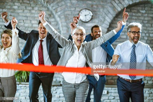 happy businesswoman crossing finish line during sports race in the office. - finishing line stock pictures, royalty-free photos & images