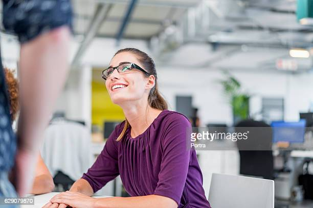 Happy businesswoman discussing with coworker