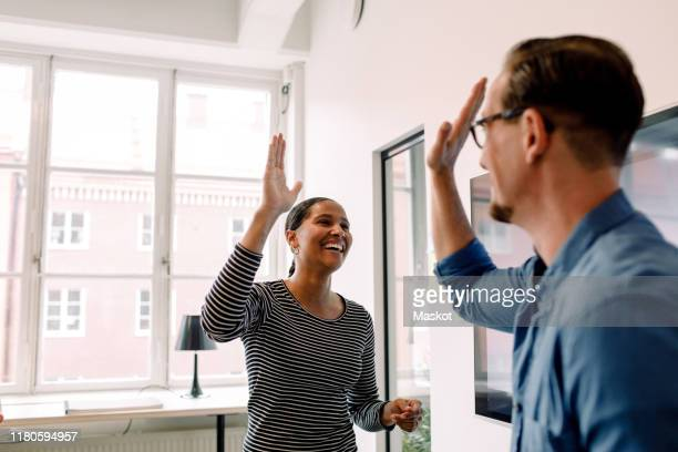 happy businesswoman giving high-five to male colleague in office - successo foto e immagini stock