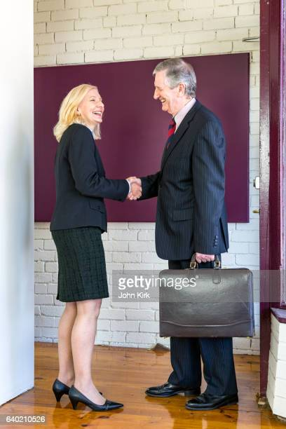 Happy businesswoman greets smiling businessman at office door