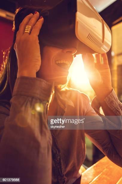 Happy businesswoman having fun while using virtual reality glasses.