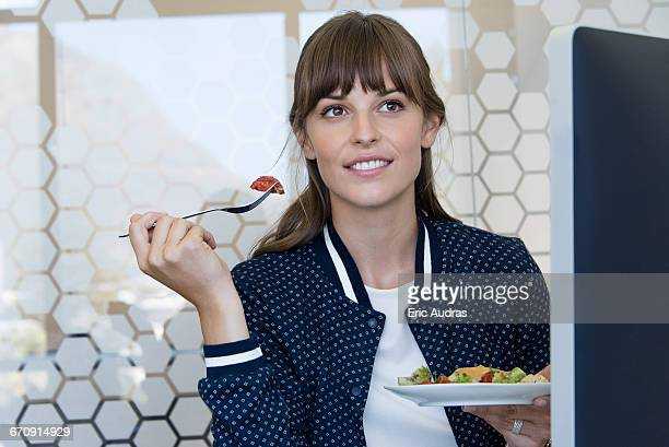 Happy businesswoman having lunch in an office