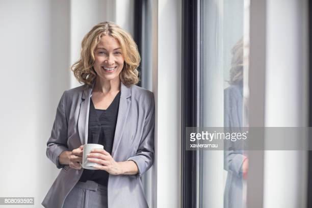 Feliz empresaria sosteniendo la taza de café por la ventana