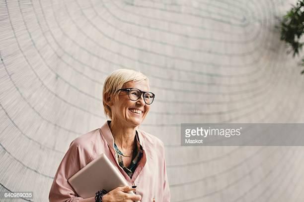 happy businesswoman holding digital tablet against wall in creative office - bürokleidung stock-fotos und bilder