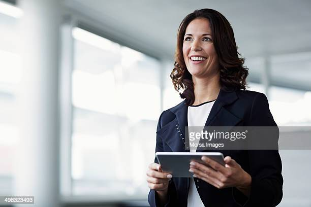 happy businesswoman holding digital tablet - wegkijken stockfoto's en -beelden