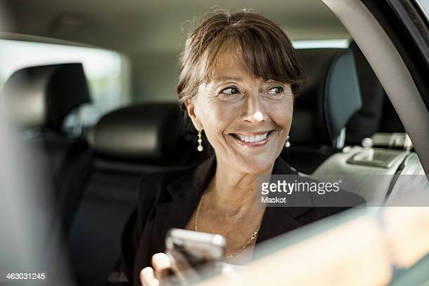 Happy businesswoman holding mobile phone looking out through taxi window