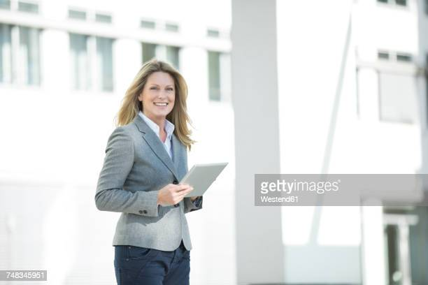 Happy businesswoman holding tablet outdoors