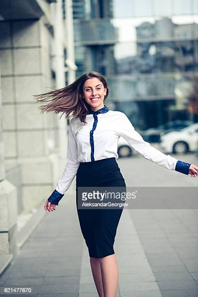 happy businesswoman how dancing outdoors on city street - skirt blowing stock photos and pictures