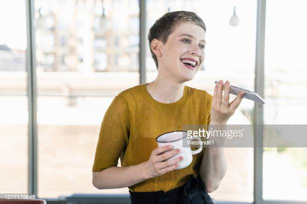 happy businesswoman in office holding coffee mug and using smartphone - one mid adult woman only stock pictures, royalty-free photos & images