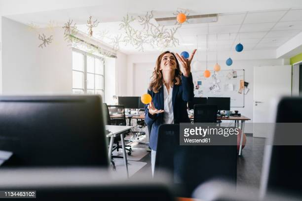 happy businesswoman juggling balls in office - juggling stock pictures, royalty-free photos & images
