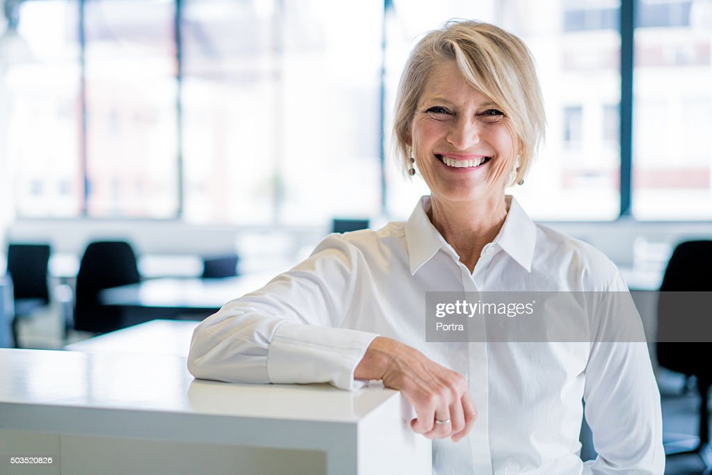 Happy businesswoman leaning on cubicle in office : Stock Photo