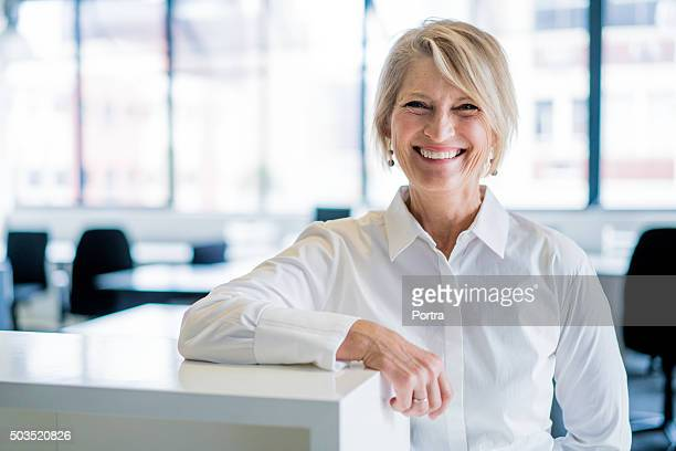 happy businesswoman leaning on cubicle in office - zakenvrouw stockfoto's en -beelden