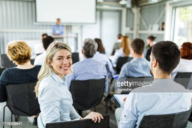 happy businesswoman looking at camera during seminar in board room. - attending stock pictures, royalty-free photos & images