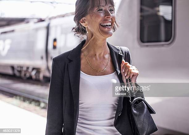Happy businesswoman looking away while standing on railroad station