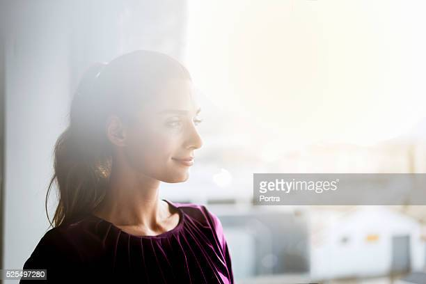 Happy businesswoman looking through window